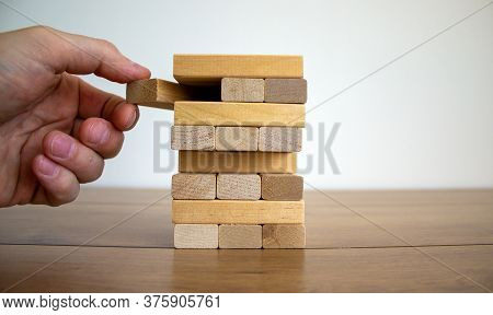 Male Hand Draws A Block From The Model Of Business, Made From Wood Blocks. Alternative Risk Concept,