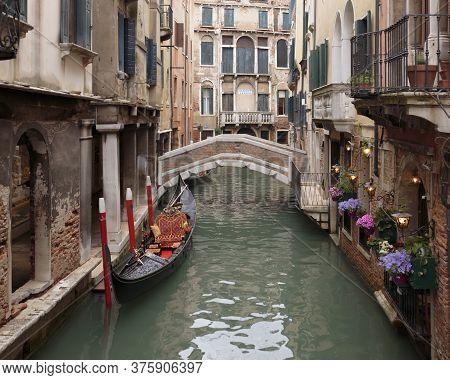 A Gondola Moored On The Rio Dei Bareteri Canal Seen From Ponte Dei Bareteri, Venice, Itally