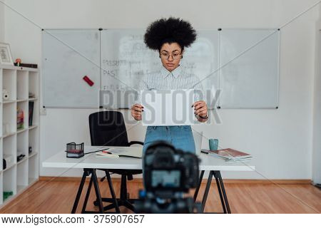 Young Afro American Female Teacher Showing A Blank Sheet Of Paper At Camera While Teaching English O