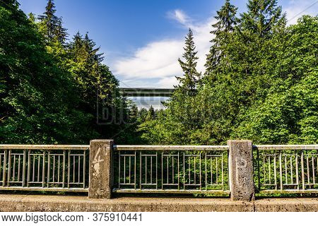 View From Bridge To Other Bridge Over Green Forest With White Clouds On The Sky