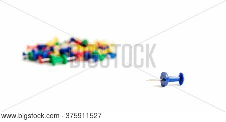 One Blue Pushpin Lies Separately From The Rest Of The Heap Of The Same Buttons On A White Background