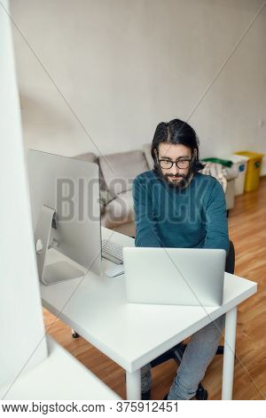 Young Focused Caucasian Bearded Man Using Laptop While Sitting At His Workplace And Working From Hom