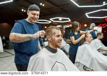 Cheerful Professional Tattooed Barber Making Haircut For A Young And Happy Handsome Man Sitting In B