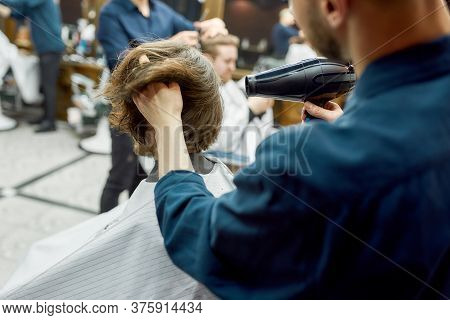 Back View Of Barber Drying Long Hair Of His Client Sitting In Armchair In The Modern Barber Shop. Ha
