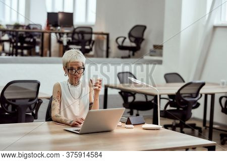 Young Concentrated Tattooed Business Woman In Eyewear Holding Cup Of Coffee And Working With Laptop