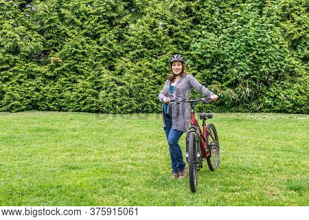 Pregnant Woman On The Green Lawn In A Park Holding Bicycle Ready To Ride.