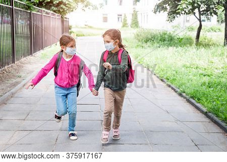 Two Girls Running Back To School During Coronavirus Pandemic. Pupils Of Primary School With Schoolba