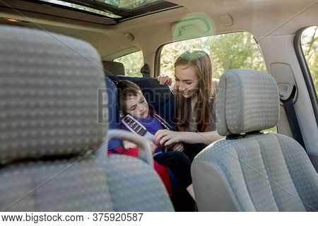Protection In The Car. Hands Of Caucasian Woman Is Fastening Security Belt To Child, Who Is Sitting