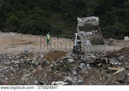 Salvador, Bahia / Brazil - April 22, 2019: Truck Is Seen Pouring Rubble Into Landfill In Salvador.