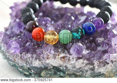 A Close Up Image Of A Beautiful Chakra Bracelet Charging On A Purple Amethyst Geode.