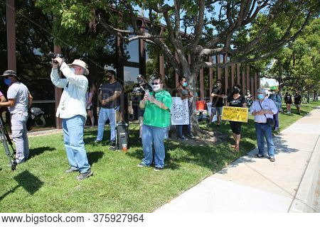 Santa Ana, CA / USA - July 11, 20202: Protesters Hold Signs, Wave Flags to protest the desire to have the name of John Wayne Airport changed to something of their liking. Black Lives Matter Protesters