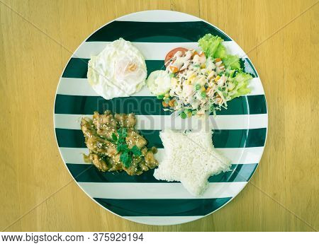 Fried Chicken With Garlic And Pepper And Fried Egg And Vegan Salad And Rice In Dish On Wood Table Wi