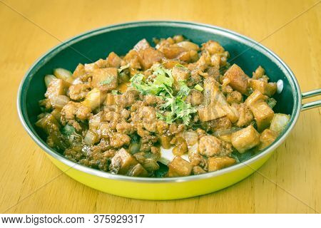 Stir Fried Pork With Onion And Garlic And Black Soy Sauce And Coriander Topping And Tofu In Pan On W