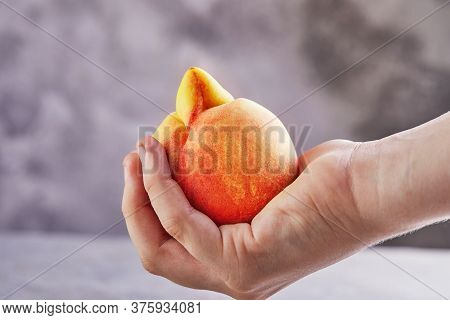 An Ugly Fruit Or Vegetable. Hand Holding A Very Ugly Peach Mutant On A Gray Background. Ugly Fruits