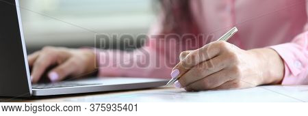Woman Makes Notes With Pen On Sheet And On Laptop. Atmosphere Activity Is Very Conducive To Fruitful