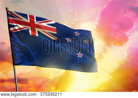 Fluttering New Zealand Flag On Beautiful Colorful Sunset Or Sunrise Background. New Zealand Success