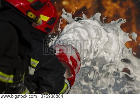Firefighter Puts Out A Fire. Silhouettes Of Firefighters With Hoses With Foam On A Background Of Fir