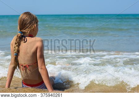 A Girl Sits On A Sandy Sea Beach And Looks Into The Distance
