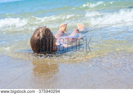 A Girl Lies On Her Back In Shallow Water On The Sea Sandy Coast