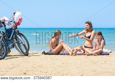 Children And Mother Eat While Sitting On The Seashore, Bicycles Are Nearby
