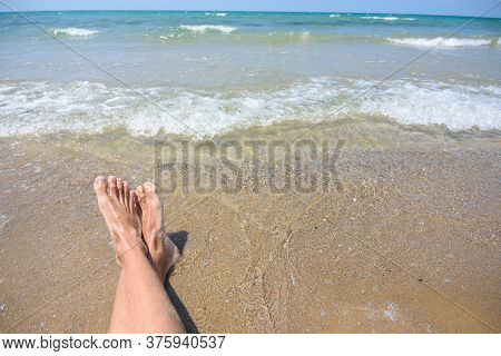 Feet Of A Man On A Sandy Beach, In The Background A Sea Surf And Horizon