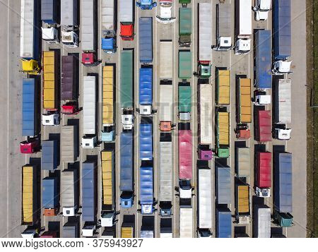 Many Trucks In The Parking Lot, A Queue Of Trucks For Unloading. Top View. Concept Of Transportation