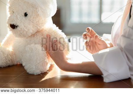 Close Up Little Girl Pretending Doctor Vaccinating Toy Bear