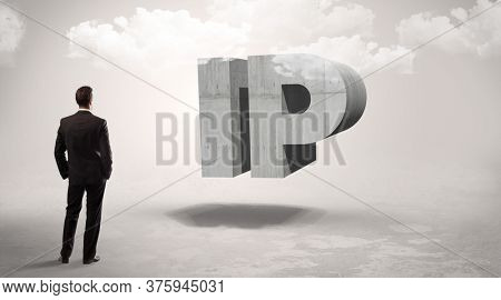 Rear view of a businessman standing in front of IP abbreviation, modern technology concept