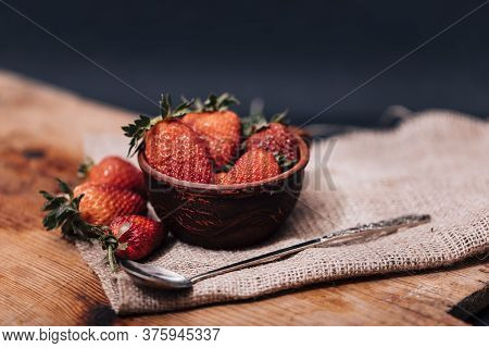 Fresh Strawberries In A Brown Bowl On Wooden Table In Rustic Style.