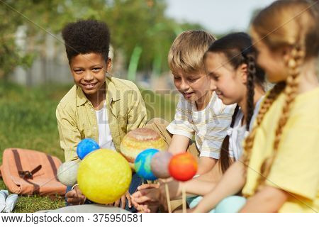 Multi-ethnic Group Of Children Sitting On Green Grass And Holding Model Planets While Enjoying Outdo