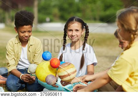 Multi-ethnic Group Of Kids Sitting On Green Grass And Holding Model Planets While Enjoying Outdoor L