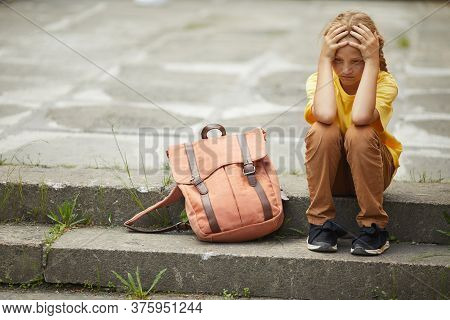 Full Length Portrait Of Sad Red Haired Schoolgirl Sitting On Stairs Outdoors Alone, Bullying And Out