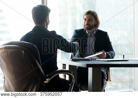 Two Smiling Young Businessmen Establishing Partnership At Meeting.