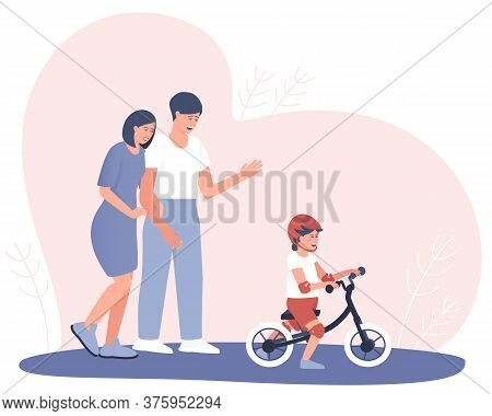 Happy Parents Watch How A Child Learns To Ride A Balance Bike. The Child Is Riding A Balance Bike In