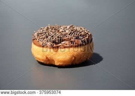 Donut. Cake Donut with Chocolate Frosting and Chocolate Sprinkles.
