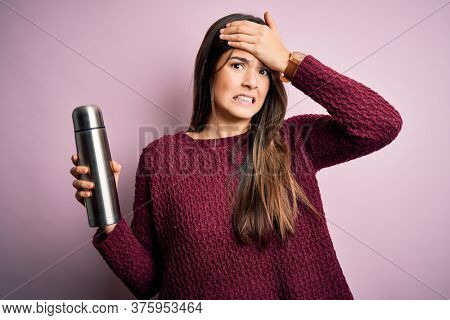 Young beautiful girl holding thermo with water standing over isolated pink background stressed with hand on head, shocked with shame and surprise face, angry and frustrated. Fear and upset for mistake