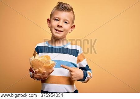 Young little caucasian kid eating unheatlhy potatoes crisps chips over yellow background very happy pointing with hand and finger