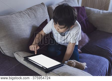 Cropped Shot Kid Sitting On Sofa Watching Cartoons On Tablet,6-7 Year Old Boy Playing Game On Touch