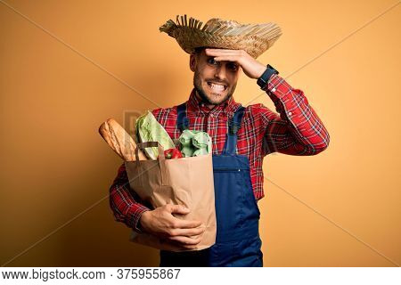 Young rural farmer man holding fresh groceries from marketplace over yellow background stressed with hand on head, shocked with shame and surprise face, angry and frustrated. Fear and upset