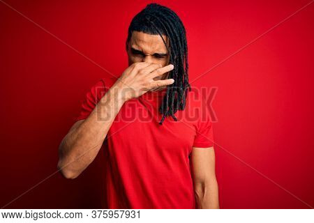 Young handsome african american afro man with dreadlocks wearing red casual t-shirt smelling something stinky and disgusting, intolerable smell, holding breath with fingers on nose. Bad smell