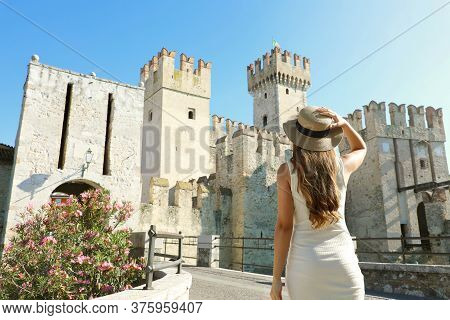 Travel In Europe. Back View Of Tourist Woman Walking In Sirmione Towards The Scaligero Castle. Rear