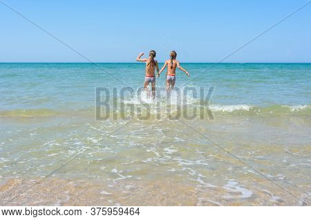 Girls Run In The Water Swimming In Shallow Water