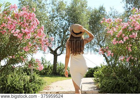Beautiful Sexy Fashion Woman Enters In A Garden Between Flowers In Sirmione On Lake Garda, Italy