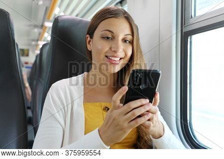 Smiling Brazilian Businesswoman Using Smartphone Social Media App While Commuting To Work In Train.