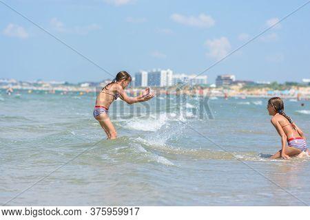 Girls Splashing On The Seashore On A Hot Sunny Day