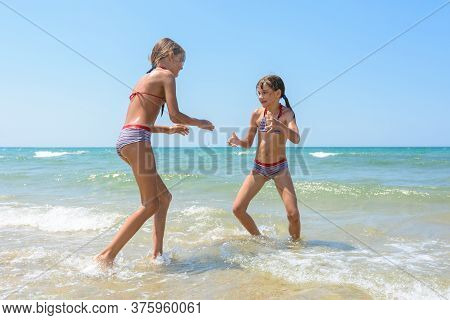 Two Girls Playing Fight On The Seashore In The Water