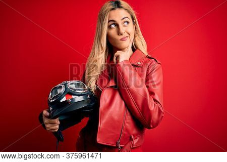 Young beautiful blonde motorcyclist woman holding moto helmet over isolated red background serious face thinking about question, very confused idea