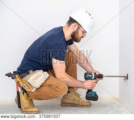 Electrician Builder At Work, Installation Of Lamps At Height. Professional In Overalls With A Drill.