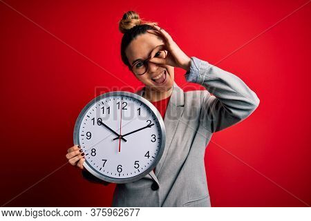 Beautiful blonde woman with blue eyes wearing glasses doing countdown using big clock with happy face smiling doing ok sign with hand on eye looking through fingers