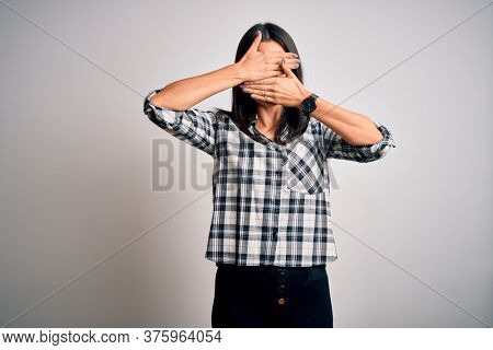 Young brunette woman with blue eyes wearing casual shirt and glasses over white background Covering eyes and mouth with hands, surprised and shocked. Hiding emotion